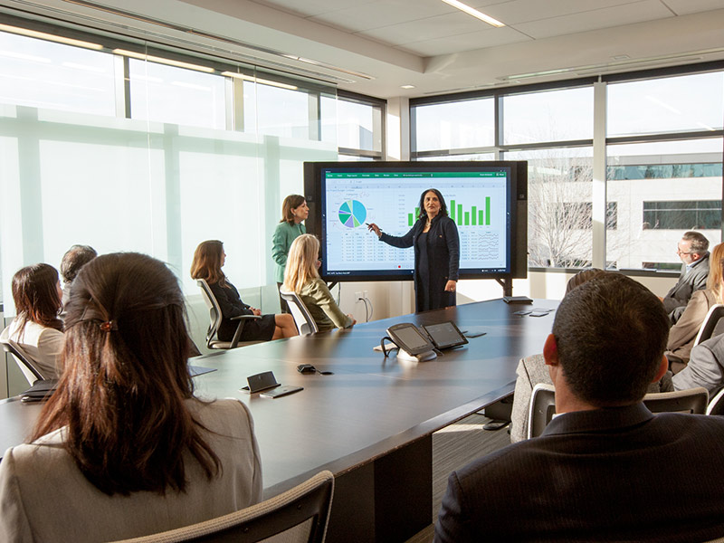 Woman presenting at large meeting in office