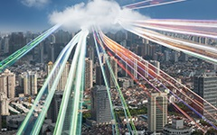Aerial view of a city with long-exposure traffic lines coming from a cloud above the city.