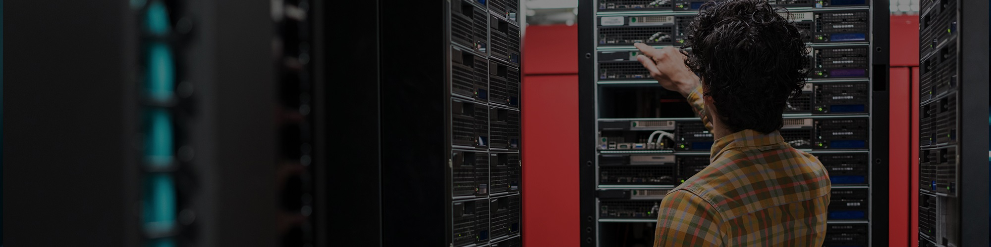 Man pointing at one server among tall stacks of servers.