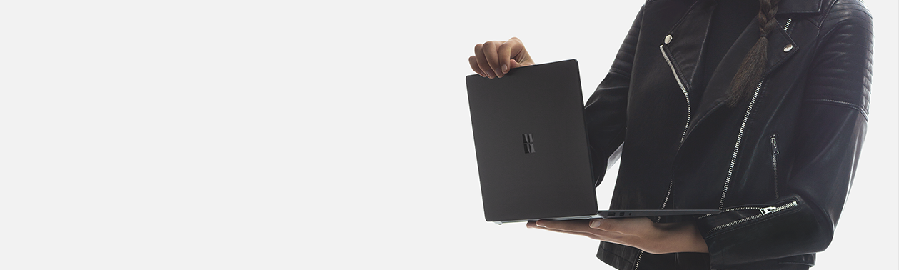 A woman holds a Surface Laptop 2