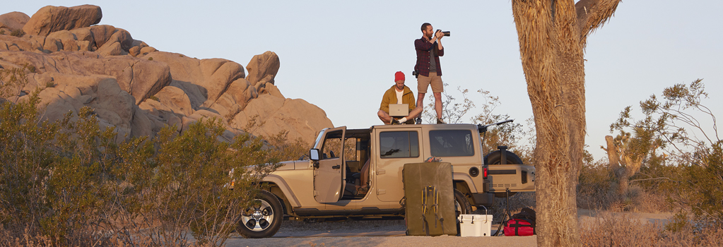 Two men on top of a jeep, one standing while taking photos and the other sitting while using a laptop