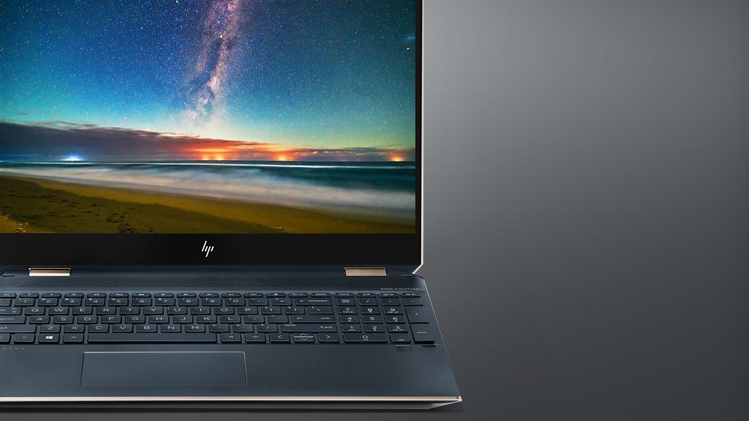 An HP Spectre x360 laptop sits open showing a 4K screen