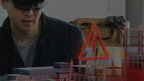Man in goggles looking at 3d building landscape with electrical safety symbol