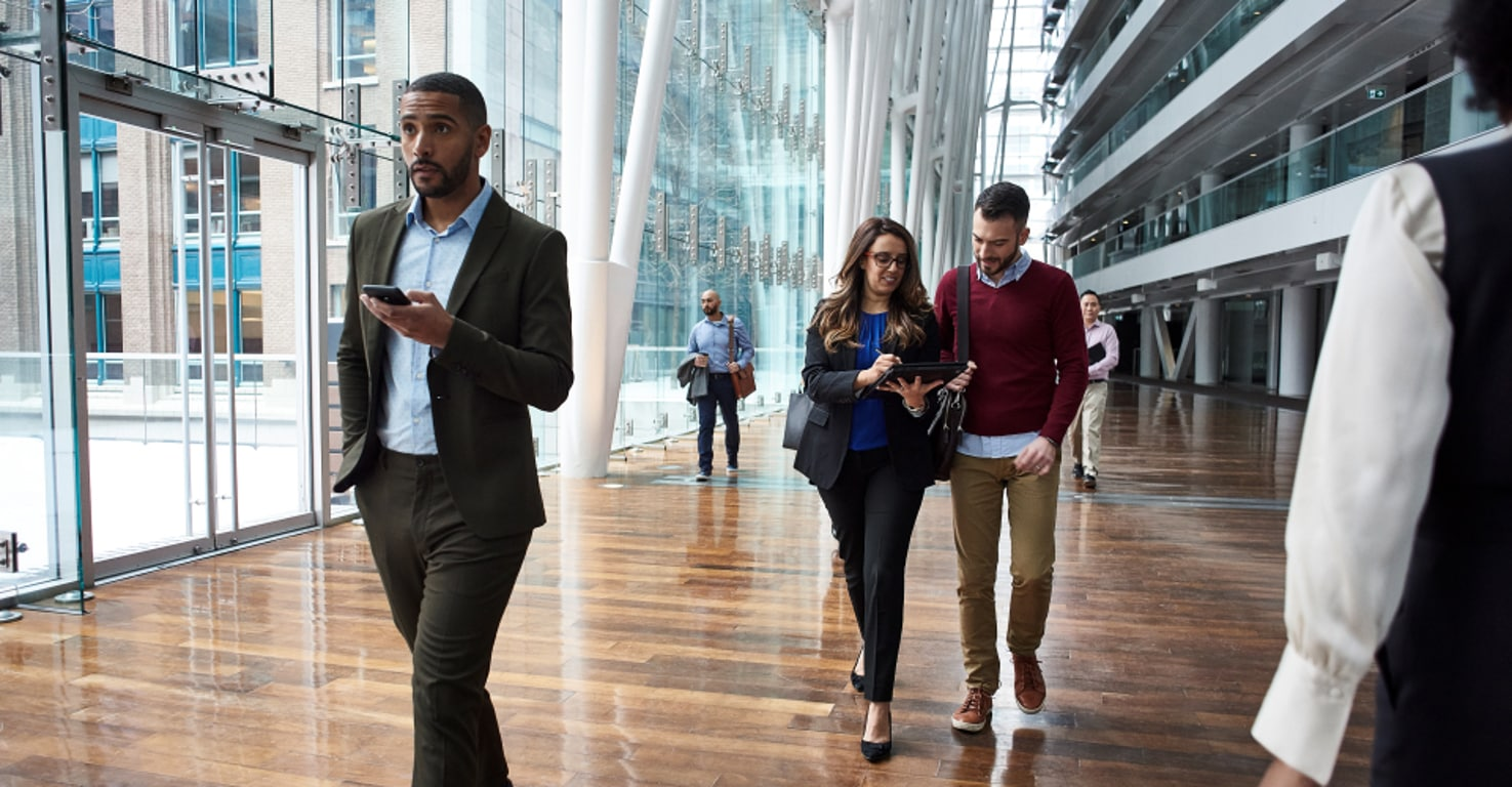 People walking through a large, glass-enclosed atrium of a modern building. One person is holding a mobile device. Two people are looking at a tablet.