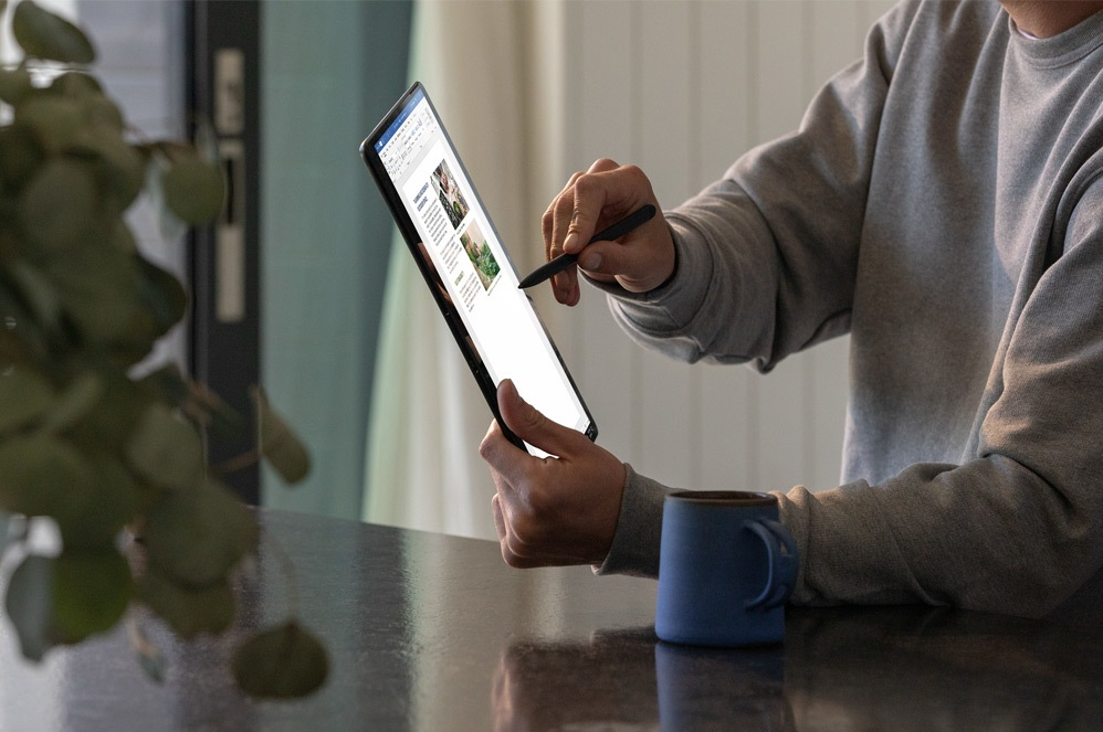 A man works in Microsoft Word on Surface Pro X in tablet mode.