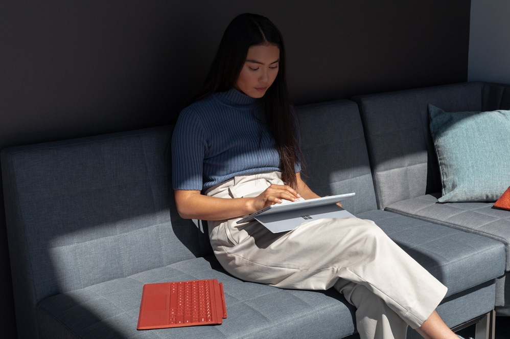 A woman works on a couch with Surface Pro 7  on her lap.