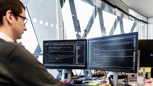 A male worker in an office setting looking at a Developer's screen on a Windows Desktop.