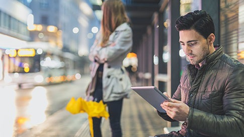 young couple waits on city street for bus while male uses laptop