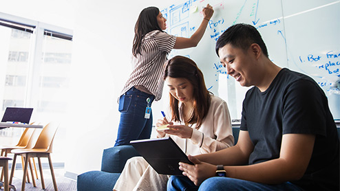 Two women and a man collaborate in an office setting with a whiteboard and Windows device