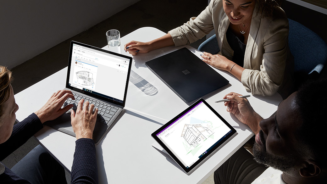 Three coworkers collaborating with their Surface Pro devices