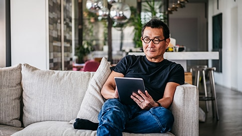 A man sitting on a couch reading on a tablet