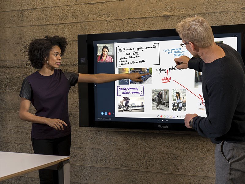 Man and woman presenting in front of a large touchscreen