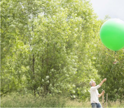 Farmer in a field releasing a camera attached to a balloon
