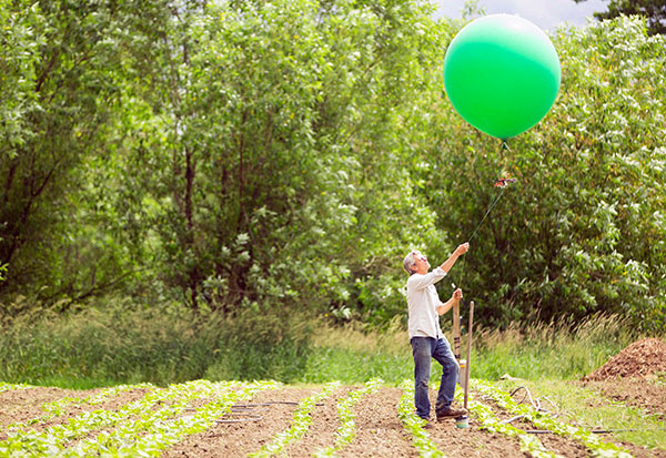 Man standing in plowed field launching a balloon