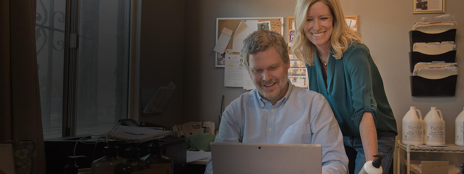 A smiling man and woman work on a PC