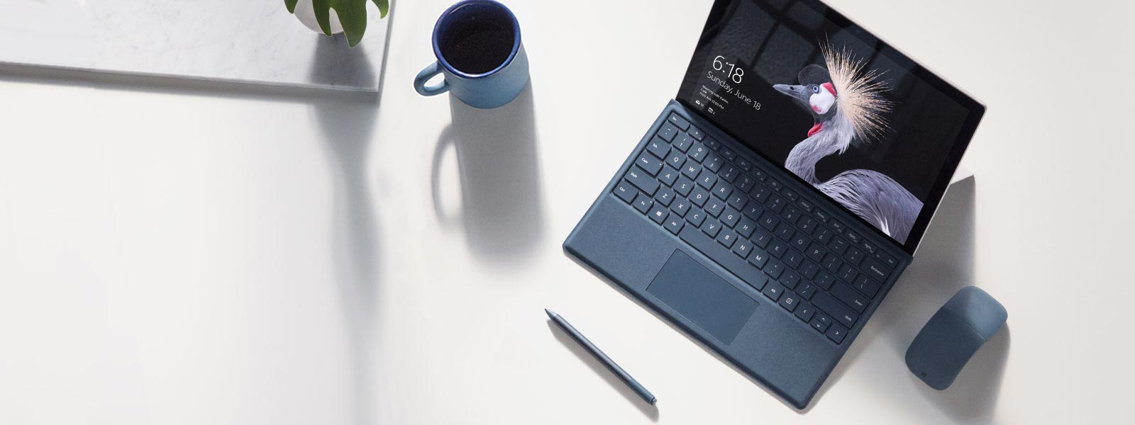 A Surface Pro on a desk with a pen and a mouse