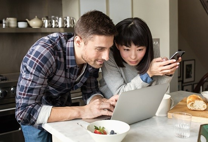 Man and woman looking at laptop on a kitchen counter.