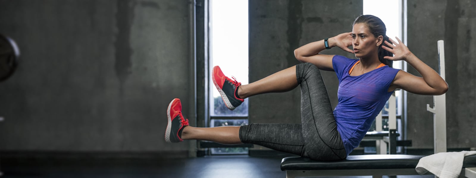 woman sitting on a workout bench in a gym doing abdominal exercises