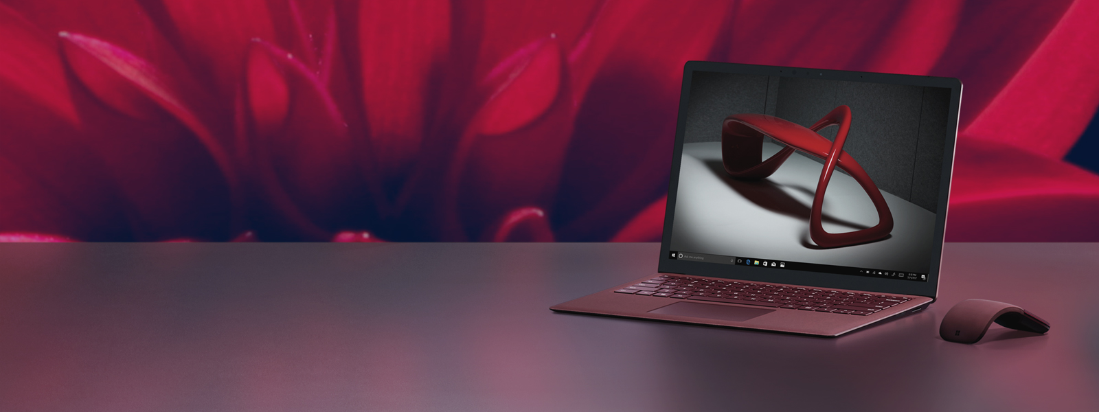A Surface Laptop showing an abstract geometric sculpture on the screen