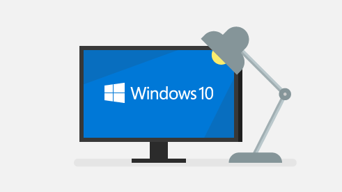 Computer screen with Windows 10 logo illuminated by a desk lamp.