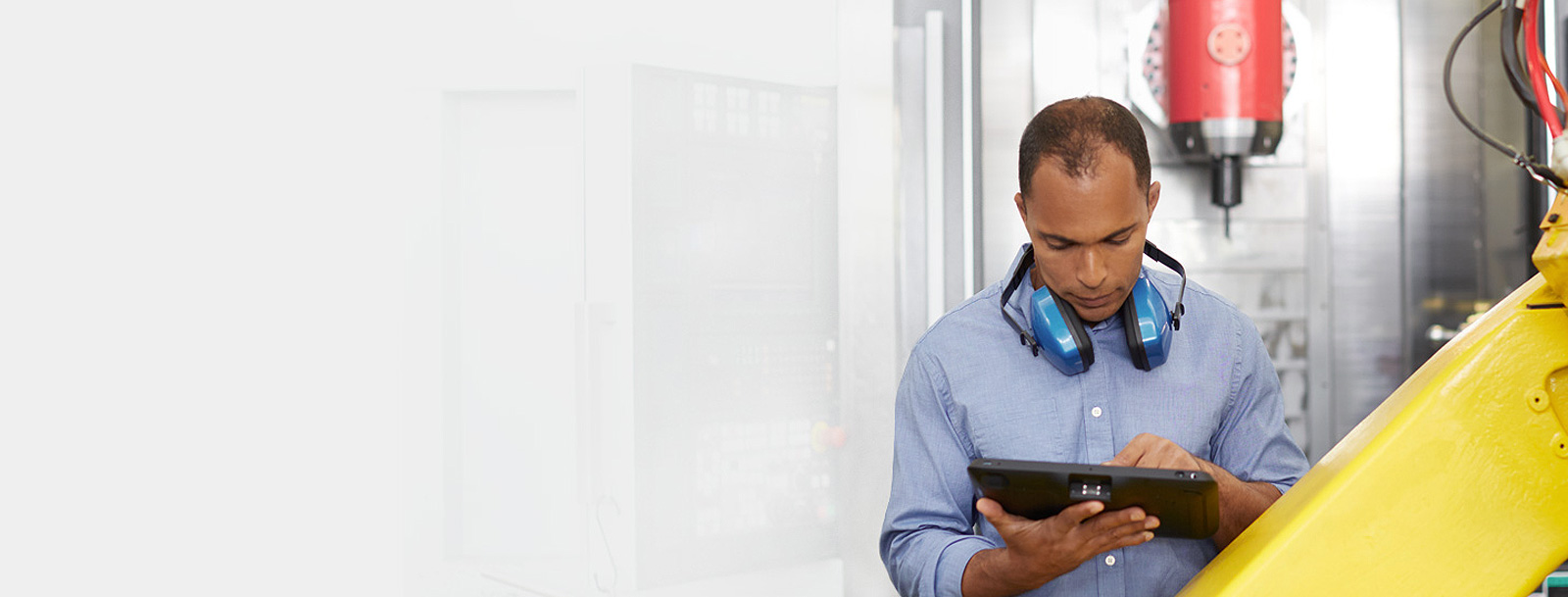 Man with protective headphones working on a tablet