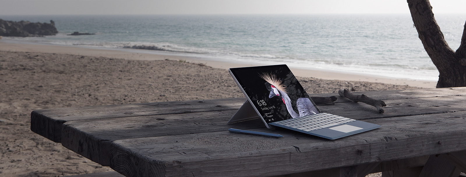Open laptop on a wood table at the beach
