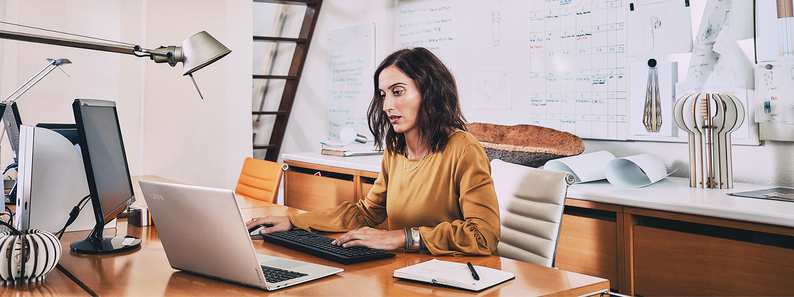 Woman sitting at office desk on computer