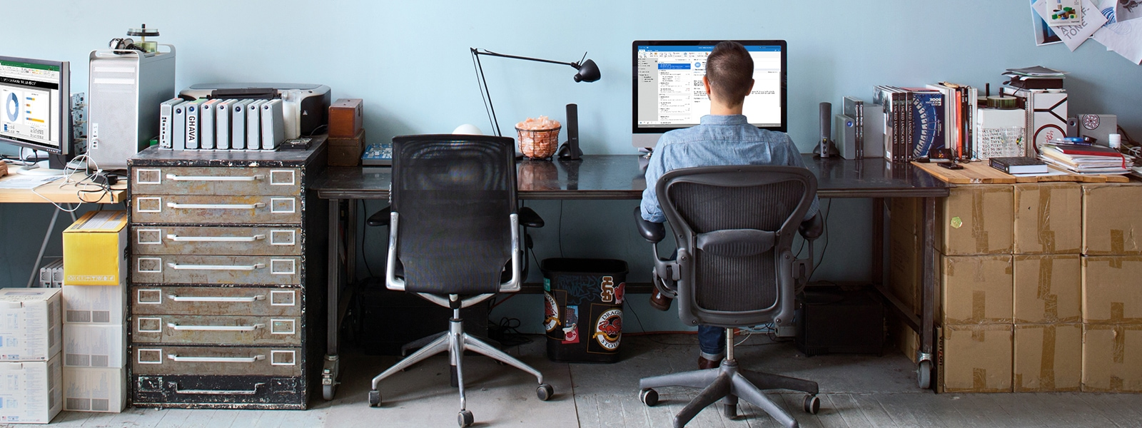 Man sitting at office desk on computer