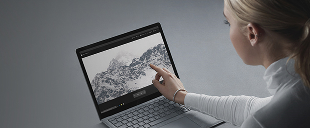 A woman touching a Surface Laptop screen