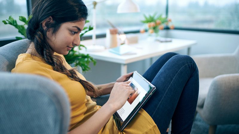 Woman sitting on chair using tablet