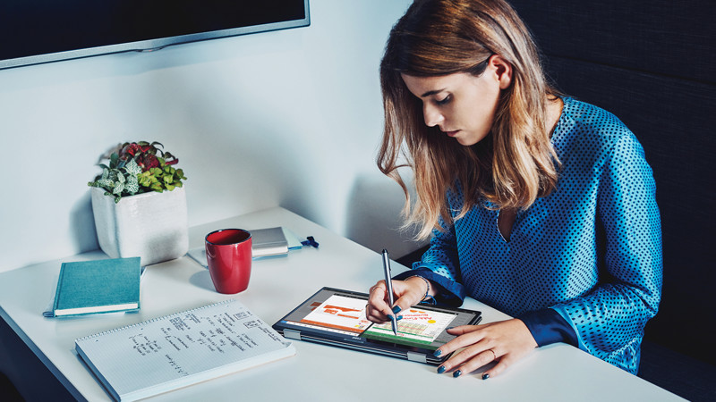 Woman writing on tablet while sitting at a table