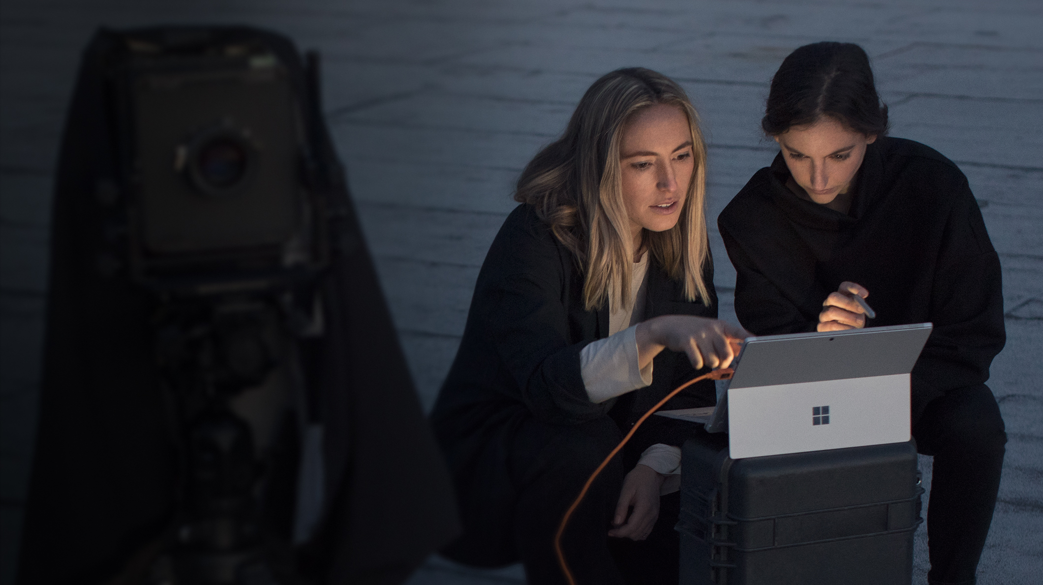 Two women look at a Surface Pro