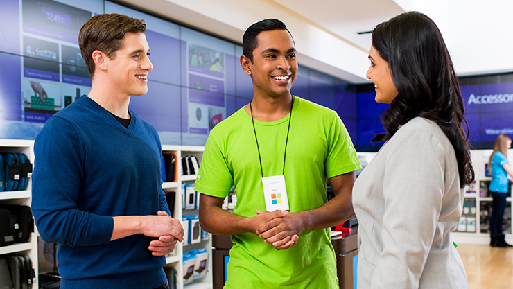 Two customers in Microsoft Store talking to employee