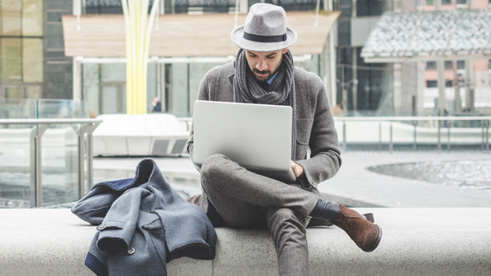 Man sitting outside in the city with his laptop