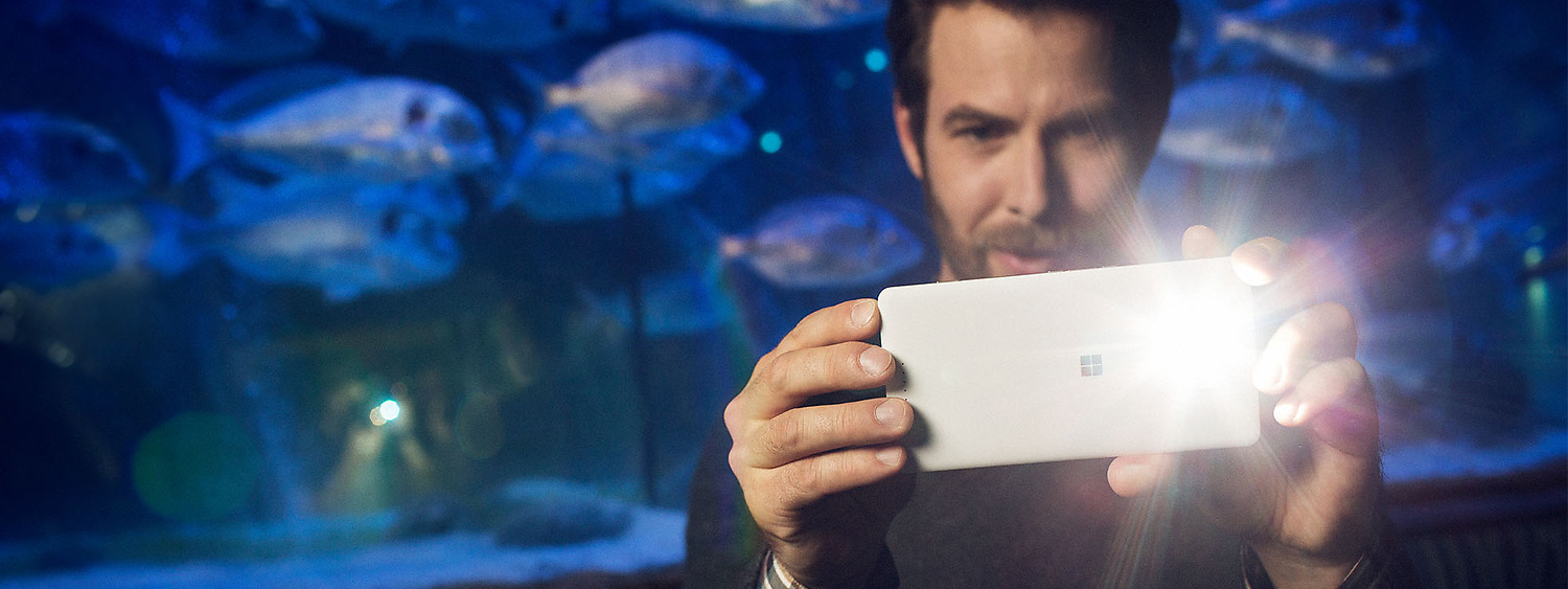 Man at aquarium taking a photo with the flash firing on his white Lumia 950 XL