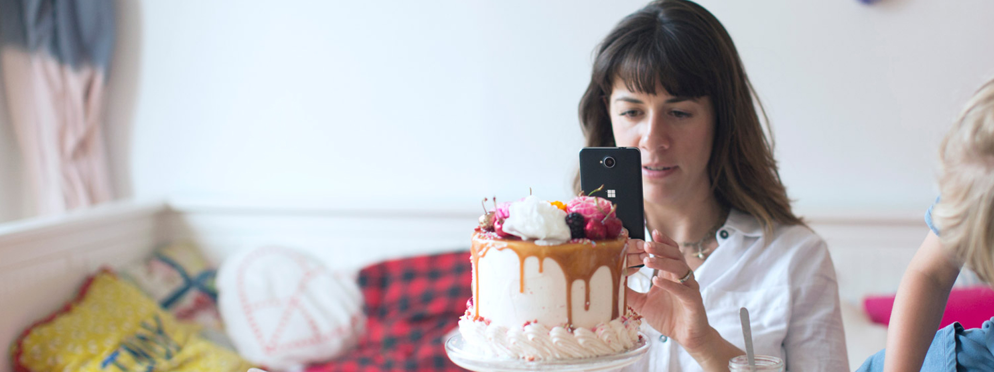 Mother taking picture of an elaborate cake on a table while daughter sitting on table plays
