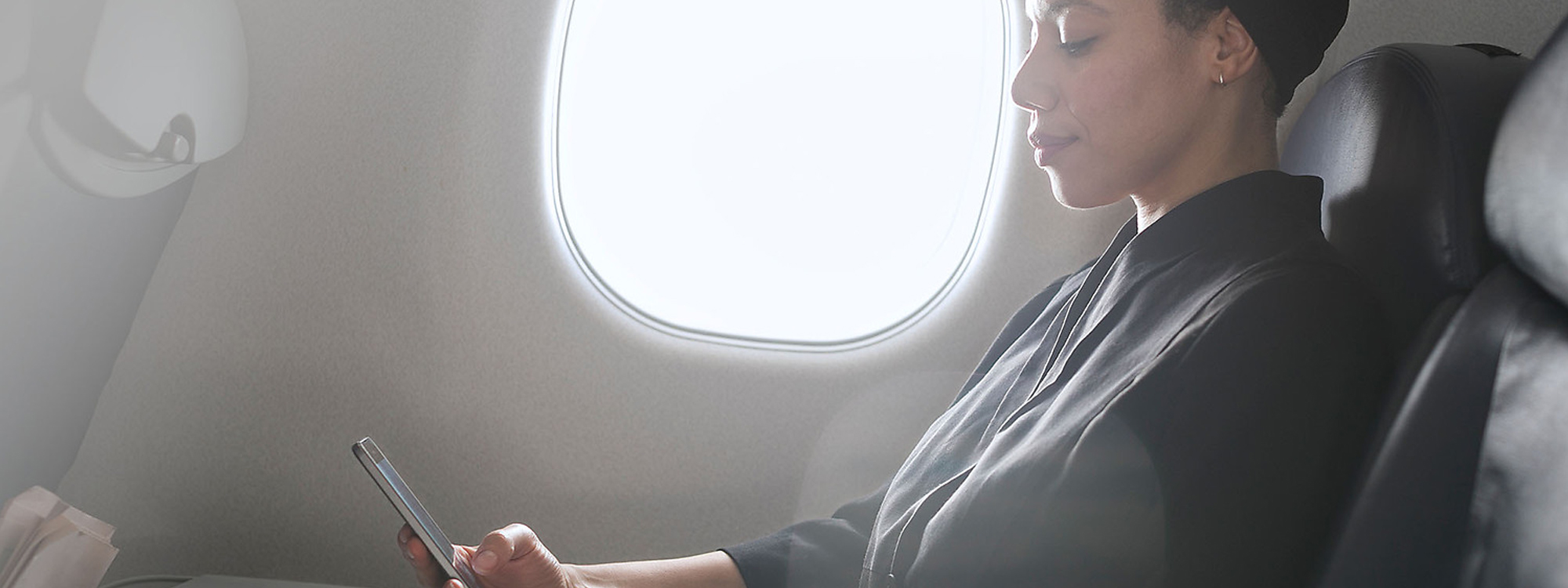 Woman sitting on plane, looking at her Lumia 650