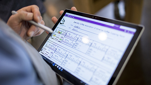 Business man holding tablet with data on screen