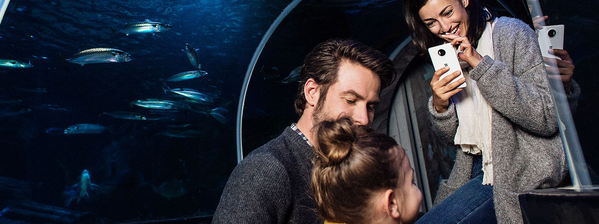 Mother using Lumia 950 XL to take a picture of father and daughter at an aquarium