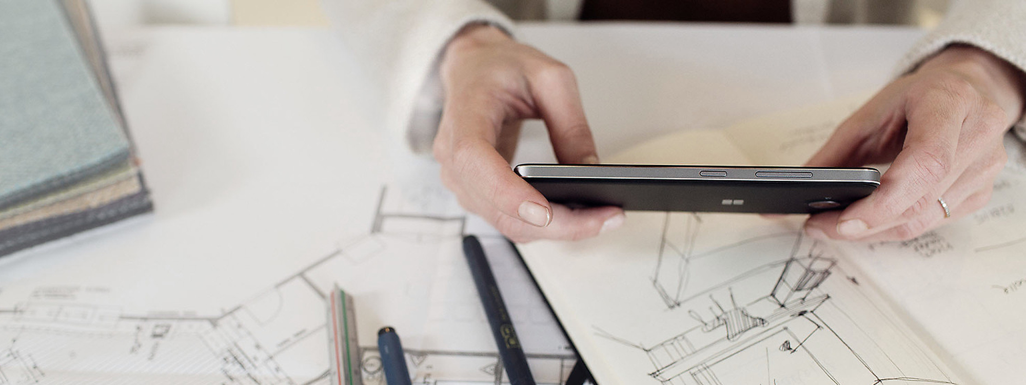 Woman's hands holding Lumia 650 over blueprints and a sketchbook on a desk