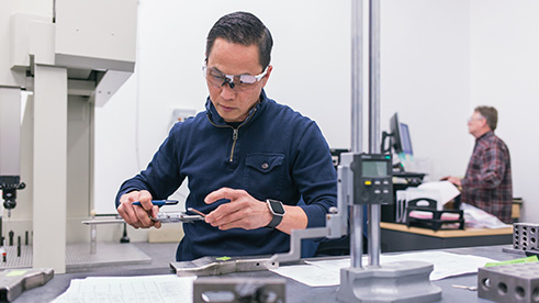 Manufacturer making precise measurements on product component