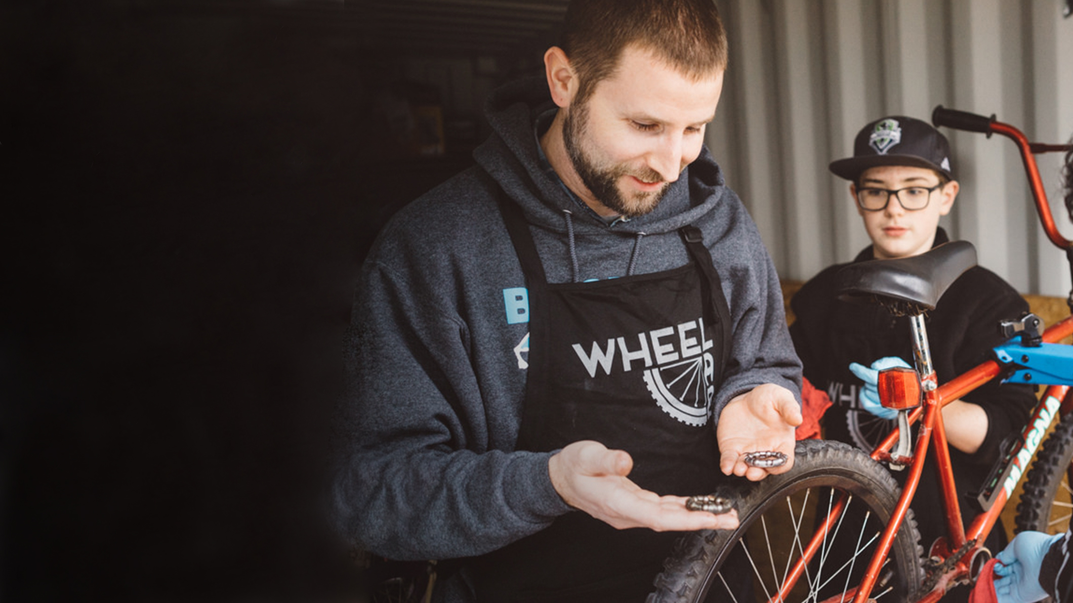 A volunteer man working on a bicycle with a kid