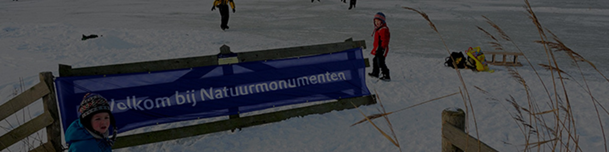 Children in the snow next to a Natuurmonumenten banner.