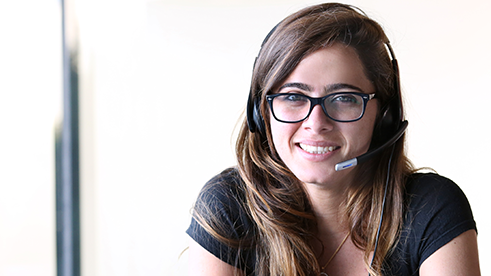 A woman smiling at the camera with a headset