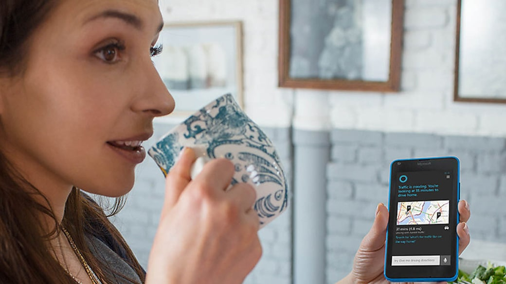 Woman drinking out of a mug, showing a a Cortana screen on her Lumia 640