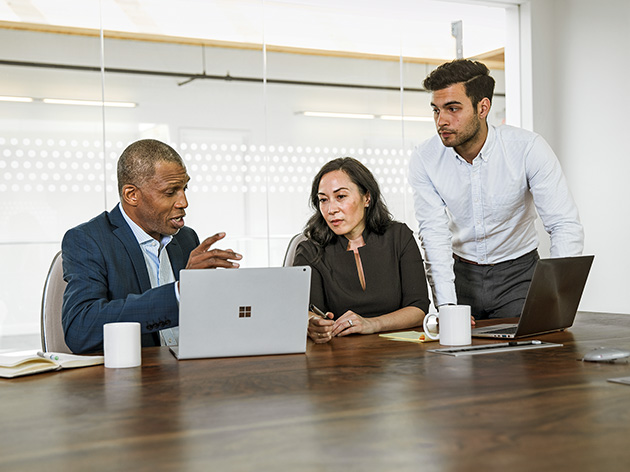 A group of people are in discussion with their laptops open in a meeting room