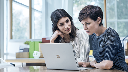 Female professionals at work using Surface Book.