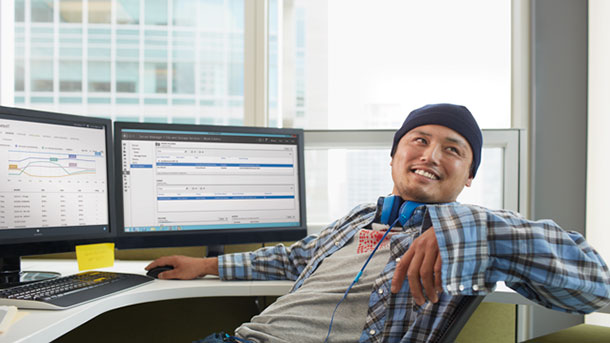 A worker smiling while navigating between applications.