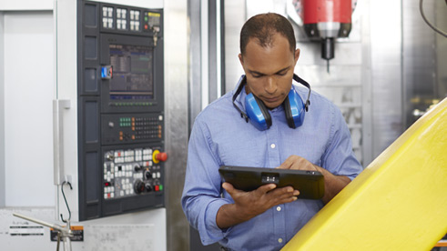 Man working in datacenter and entering data into a mobile device