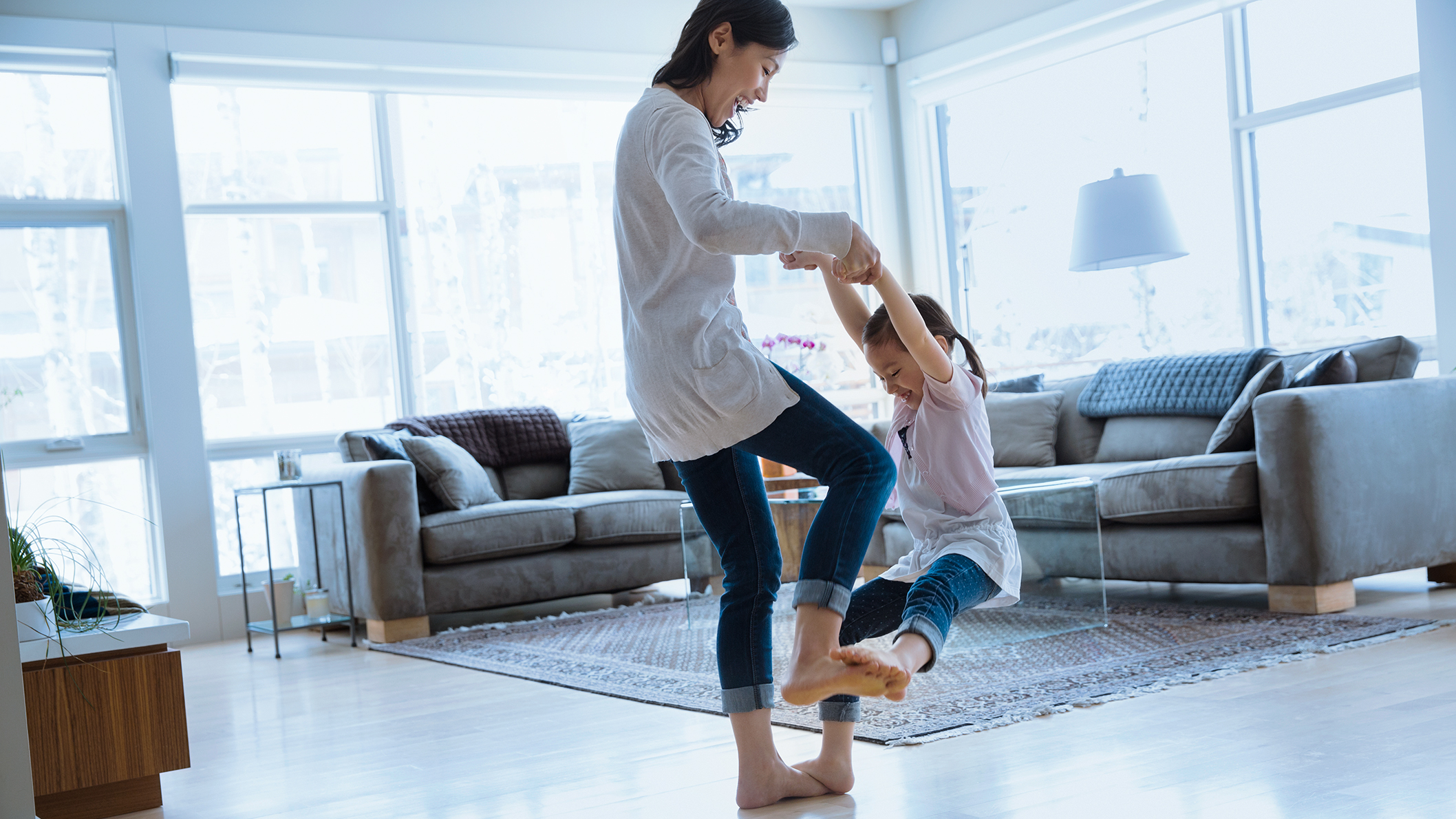 Mother dancing with daughter in living room